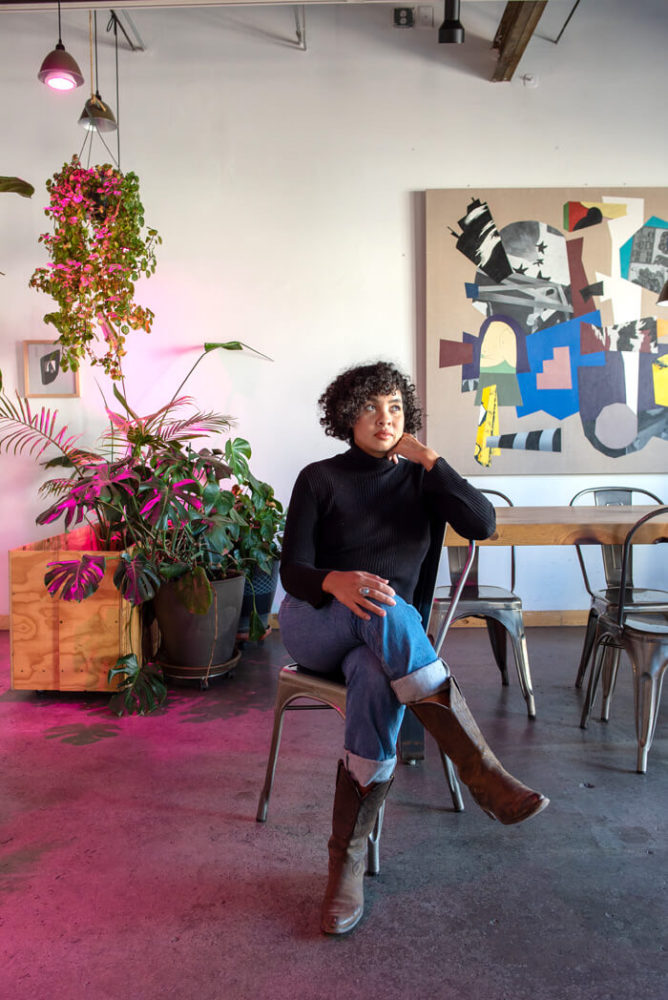 Monique Carr sitting in chair with plant and abstract painting in background