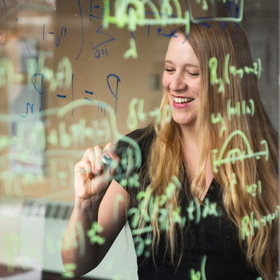Dr. Stefani Crabtree smiles as she writes equations on a clear board in green pen.